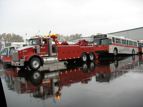 A tow-truck gets ready to haul a trolley away.