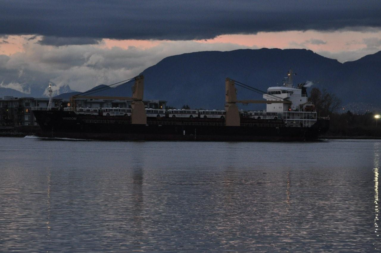 The Wisdom and her load of trolleys sail under a dark cloud approaching the Massey Tunnel. Photo by Terry Muirhead.