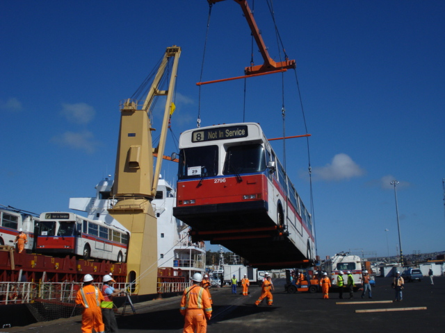 The retired New Flyer trolleys, being offloaded at the docks in San Antonio, Chile.