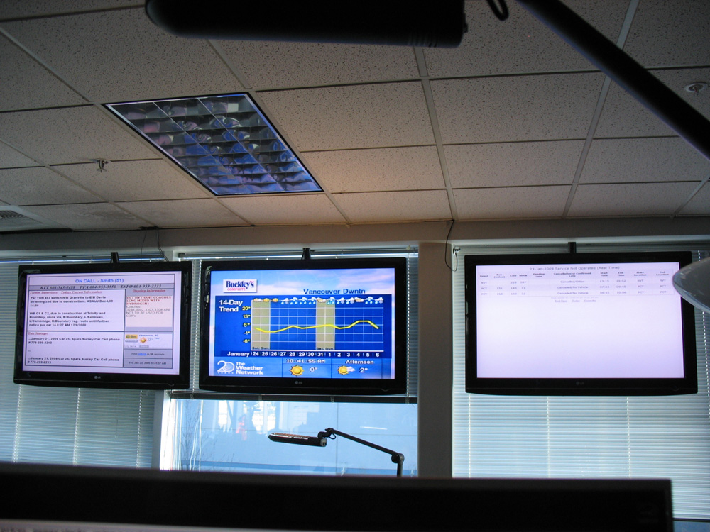 The three info screens hanging from the ceiling at T-Comm. Another set hangs along the wall to the left of this photo.