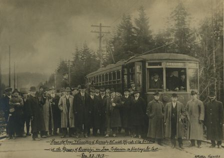 The opening of the Hastings Street Tramline Extension at Capitol Hill, Dec. 23, 1913. The 10,000-foot extension expanded a Vancouver streetcar route into Burnaby, from Boundary Road to Ellesmere Avenue. Joe Toffaletto wears the light-coloured coat near the photo's centre: he headed the BCER construction team that built this line and also anchored the BCER tug-of-war team. Reeve McGregor of Burnaby is near the tram door, wearing a bow-tie and holding a pipe in one hand and a cane in the other, and Councillor Eber Stride is in front of the tram, in a three-piece suit with white shirt and bowler hat. The rest are unidentified, although other Burnaby councillors and BCER officials are said to be pictured. (Item 166-001, from the Burnaby Historical Society Community Archives Collection, courtesy of the City of Burnaby Archives.)