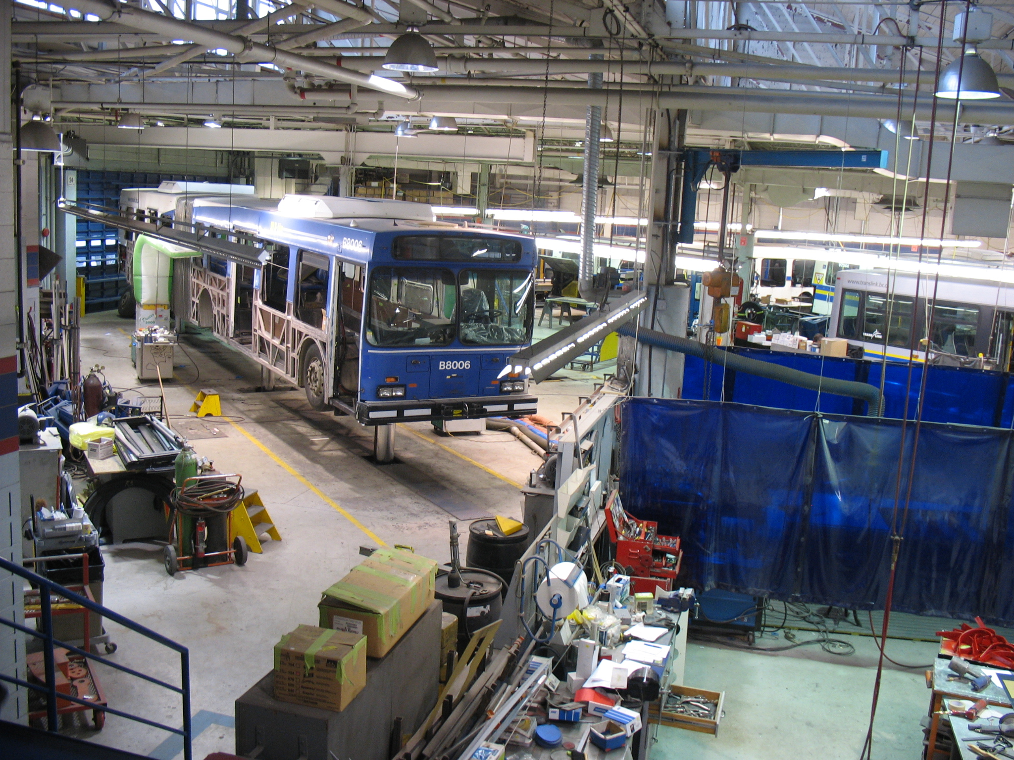 Another view of the articulated bus getting a mid-life overhaul. Notice that its lower body panels have been stripped off!