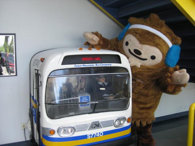 Quatchi plays with a miniature bus at Surrey Transit Centre.