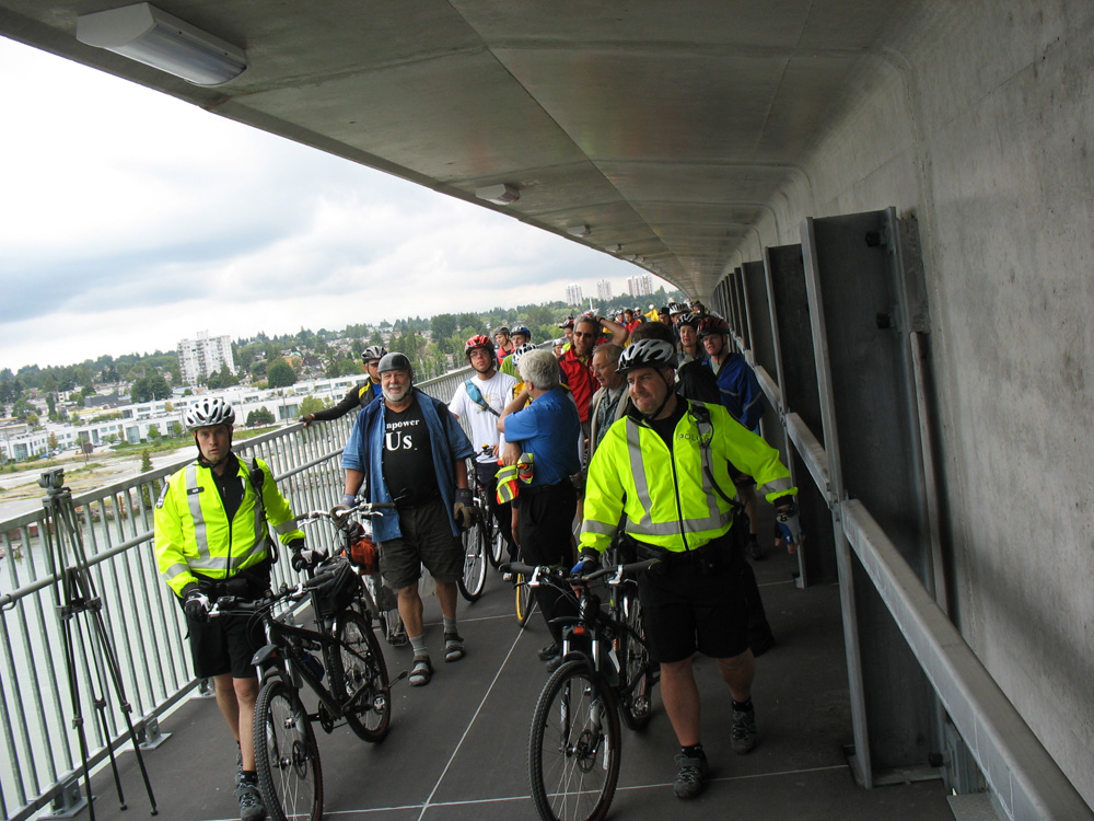 Led by the Transit Police, cyclists and pedestrians take a ceremonial first walk across the Canada Line bike and pedestrian bridge on its opening day.