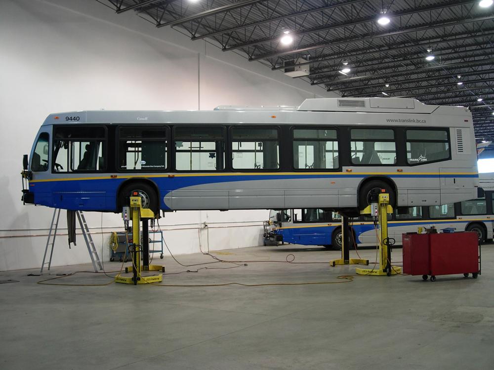 A Nova hybrid bus up on hoists at the garage!