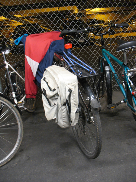 A rear rack on a bicycle with a pannier. This bike also has bungee cords on the rack, which help strap items down.