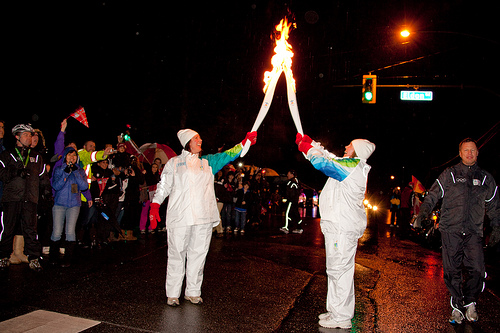 Chelsea from CMBC (right) receives the flame from the previous torchbearer on the North Shore.