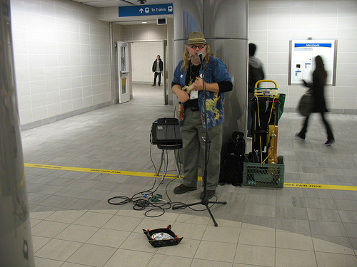 A busker next to the ticket machines at Waterfront Canada Line station.