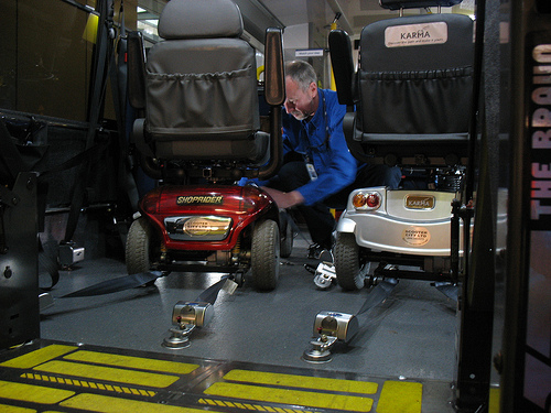 Dave secures the scooters in the HandyDART vehicle.