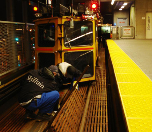 Speeder Crew repairs loose LIM cap bolts at Main Street SkyTrain Station.  File photo.