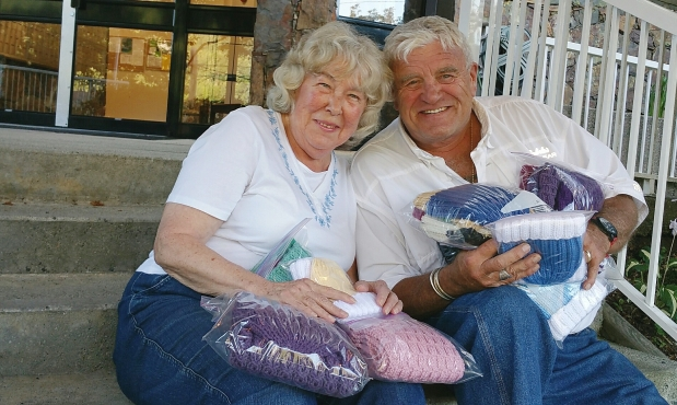Joy Clapper and Bus Operator Glen Foster hold knitted items that will be donated to the Helping Hand charity