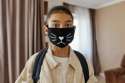 a little girl wearing a mask