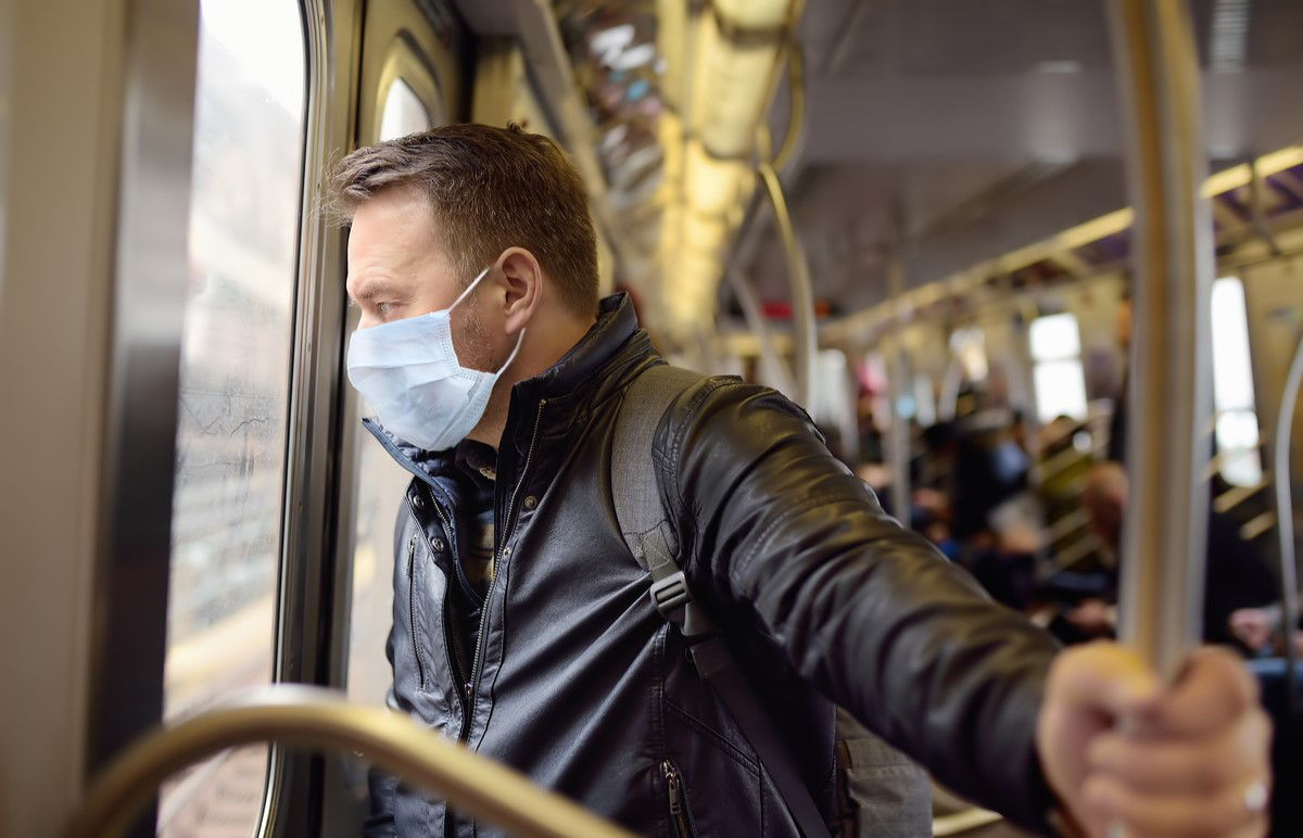 man commuting on the Skytrain with a face mask