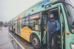 Bus operator standing at the door of a bus
