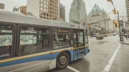 A bus driving on Burrard Street in downtown Vancouver