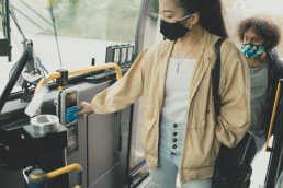 Customer with a mask boarding the bus and tapping their Compass Card