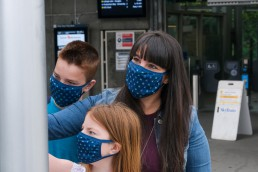 A mom and two children wearing masks looking at a transit map