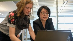 Alycia Butterworth and a colleague looking at a computer screen