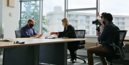 Two TransLink executives sit at a table in a boardroom while a film crew captures the moment.