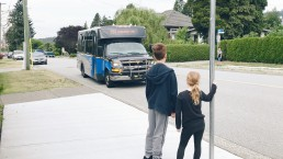 A pair of kids wait for the 157 Lougheed Station bus