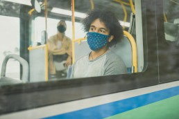 A young man sits on the bus wearing a mask.